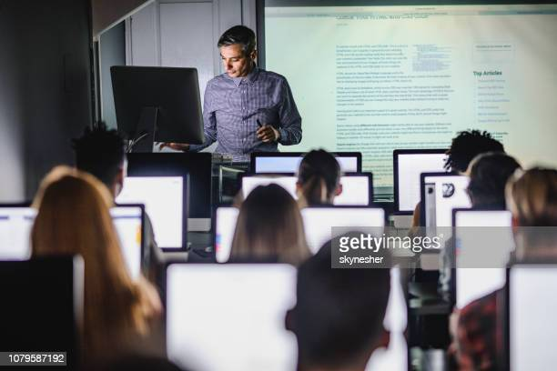 mid adult professor teaching a lecture from desktop pc at computer lab. - classroom stock pictures, royalty-free photos & images