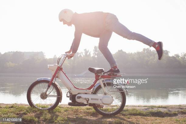 mid adult riding moped, doing stunt, beside lake - mobylette photos et images de collection
