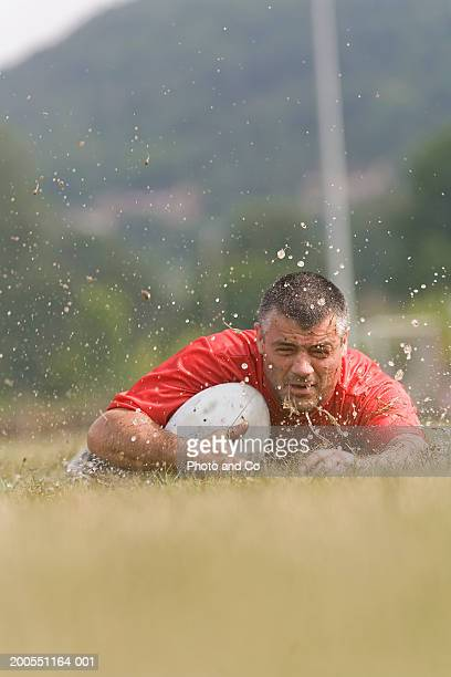 Mid adult rugby player falling into mud, ground view