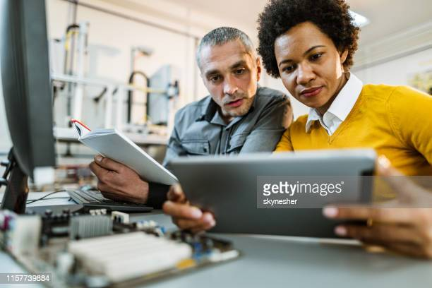 mid adult scientists using digital tablet while working on new tech project. - computer software stock pictures, royalty-free photos & images