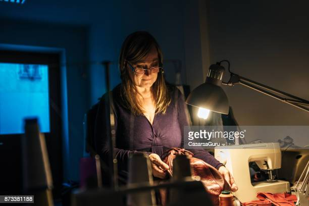 mid adult seamstress woman working at night - mid adult stock photos and pictures