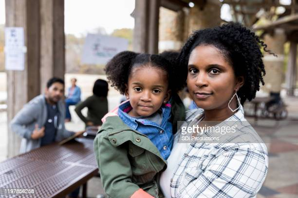 mid adult single mother holds young daughter at free clinic - serious stock pictures, royalty-free photos & images