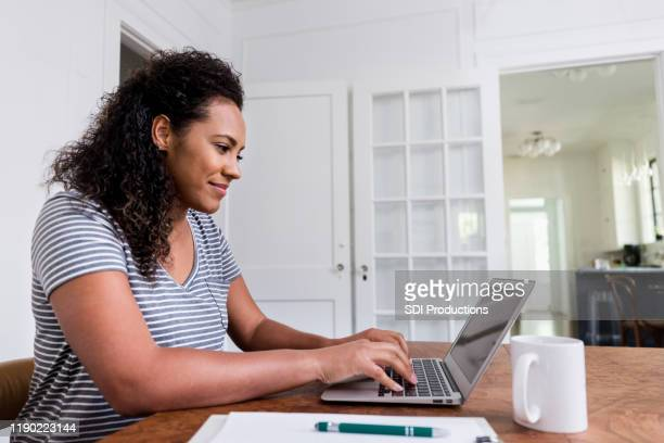 mid adult stay-at-home mom working on freelance job - stay at home mother stock pictures, royalty-free photos & images