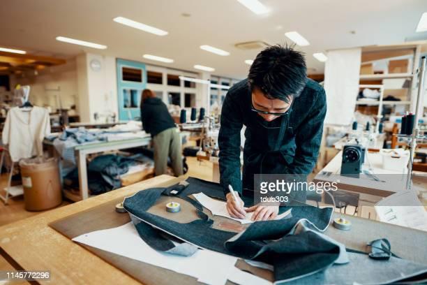sarto adulto medio che taglia il denim attorno a un modello in preparazione per realizzare un paio di jeans - jeans foto e immagini stock