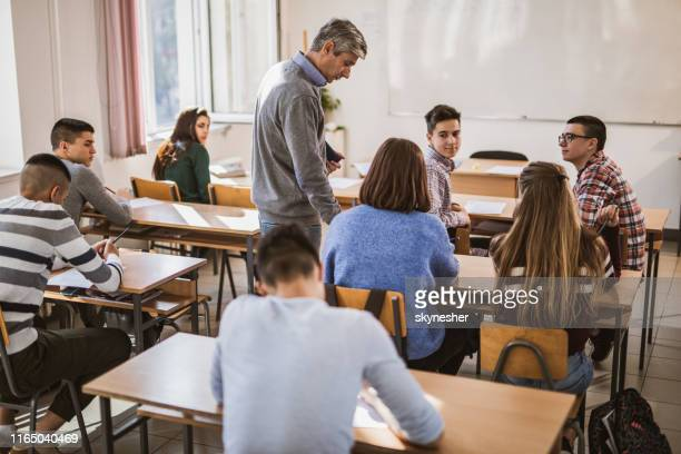 mid adult teacher assisting his students on a class at high school. - high school building stock pictures, royalty-free photos & images