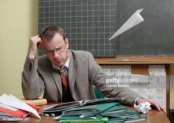 Mid adult teacher at desk, paper airplane flying toward him