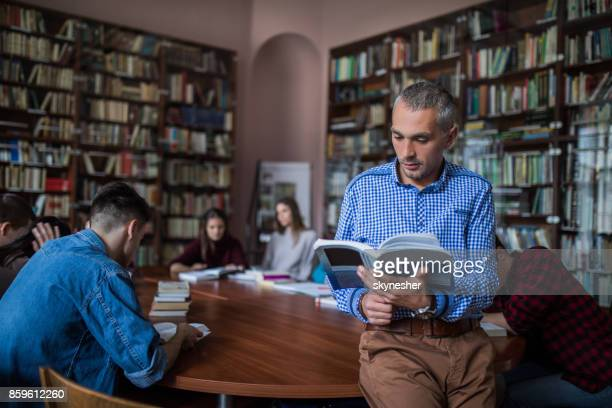 mid adult teacher reading a book in the library. - literature stock pictures, royalty-free photos & images