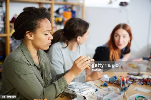 mid adult technician with equipment by young female colleagues at workshop - inventor stock pictures, royalty-free photos & images