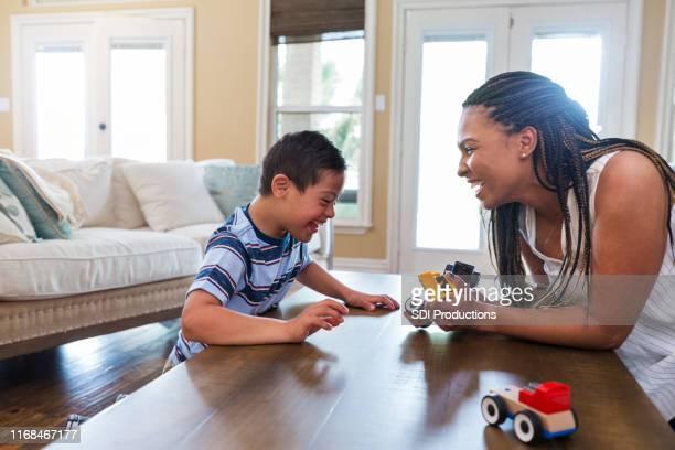 terapeuta adulto medio utiliza la terapia de juego con el niño joven - adopción fotografías e imágenes de stock