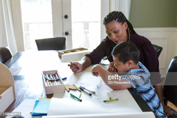 mid adult therapist works with young boy at home - childhood stock pictures, royalty-free photos & images