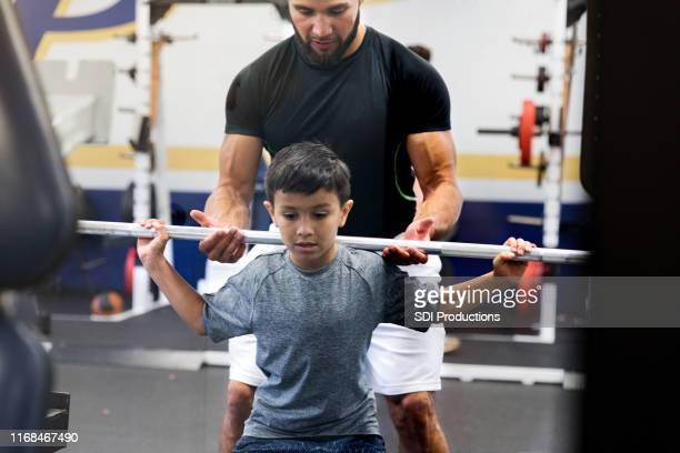 ミッド大人の叔父は、適切な重量挙げフォームで甥を助けます - kids weightlifting ストックフォトと画像