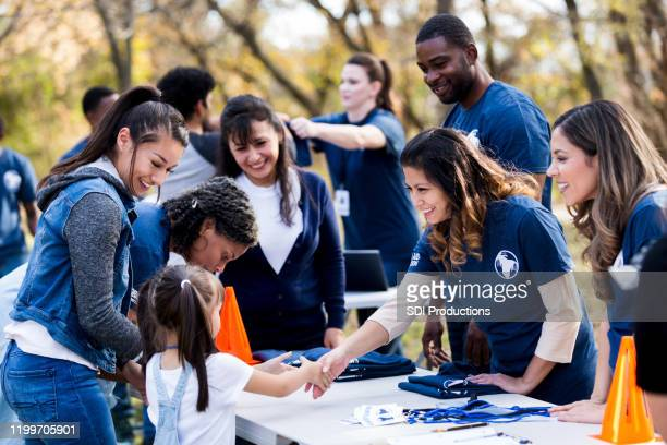 mid adult volunteer shakes hands with girl at registration table - non profit organization stock pictures, royalty-free photos & images