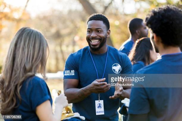 mid adult vrijwilliger praat met vrienden tijdens het evenement - friendly match stockfoto's en -beelden