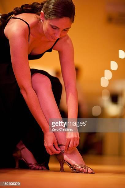 Mid adult woman adjusting strap of high heels