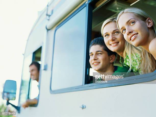Mid adult woman and a young couple looking out of a caravan window