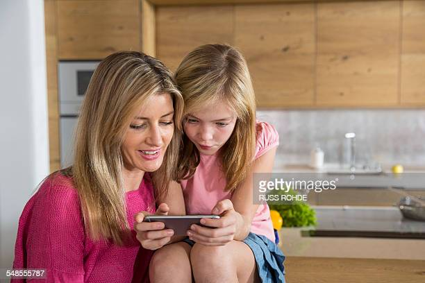 Mid adult woman and daughter reading smartphone message in dining room