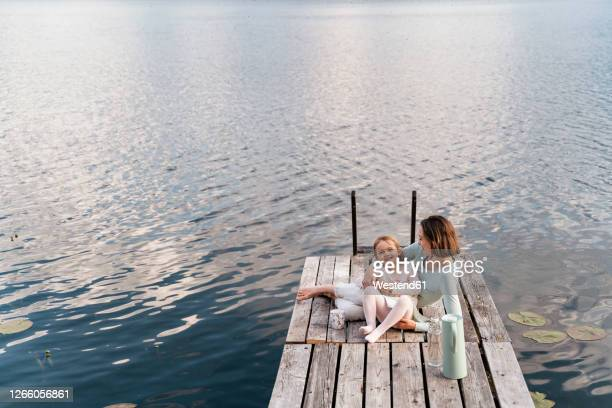 mid adult woman and daughter relaxing on jetty over lake - quayside stock pictures, royalty-free photos & images