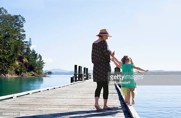 Mid adult woman and daughters playing on pier, New Zealand