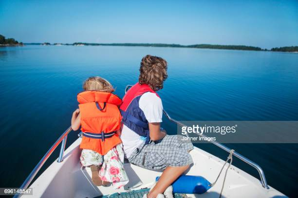 Mid adult woman and girl sitting on boats bow