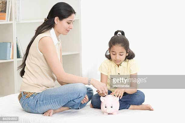 Mid adult woman and her daughter looking at a piggy bank