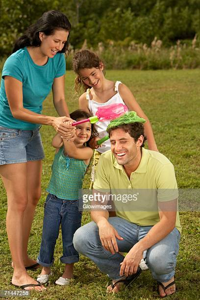 mid adult woman and her two daughters putting butterfly nets on a mid adult man's head - girl wear jeans and flip flops stock photos and pictures