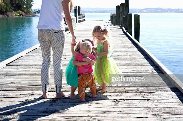 Mid adult woman and three girls on pier, New Zealand