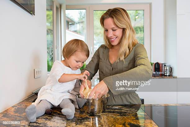 Mid adult woman and toddler daughter preparing dough in kitchen