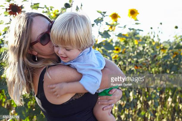 Mid adult woman and toddler hugging in sunflower field