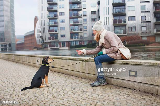 Mid adult woman and training her dog on city riverside