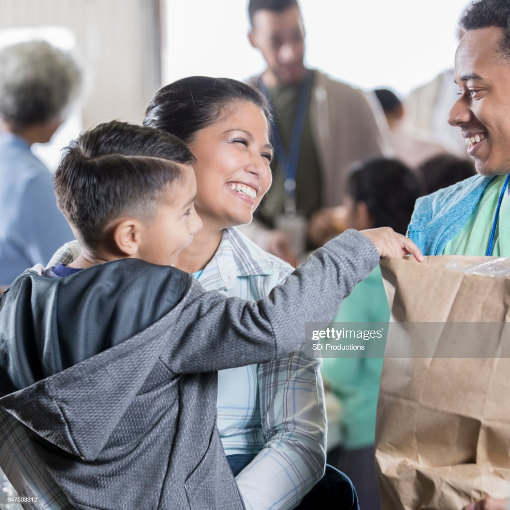 Mid adult woman and young son receive groceries at food bank : Stock Photo