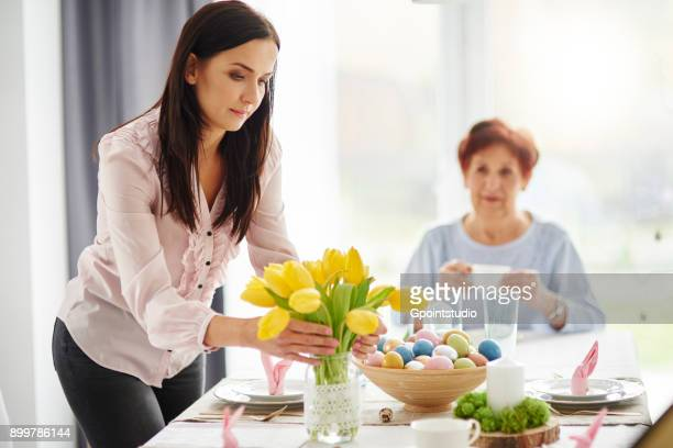 mid adult woman arranging yellow tulips at easter dining table - easter flowers stock pictures, royalty-free photos & images