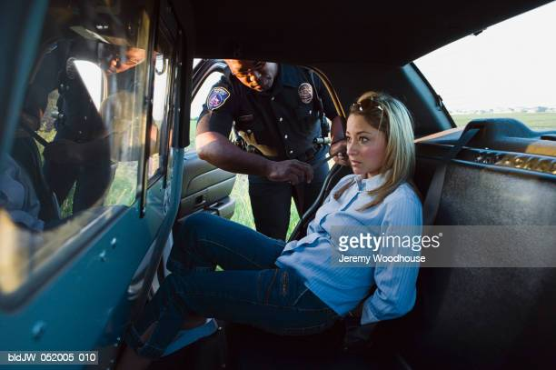 Mid adult woman arrested by a police officer sitting in a police car