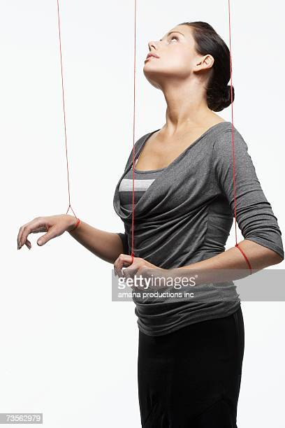 Mid adult woman as marionette looking up
