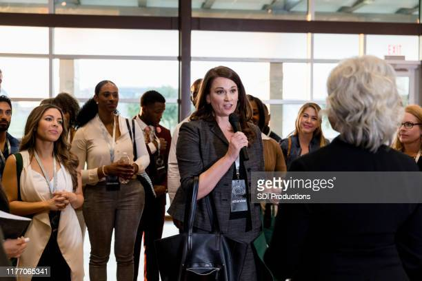 mid adult woman asks unrecognizable speaker question - town hall meeting stock pictures, royalty-free photos & images