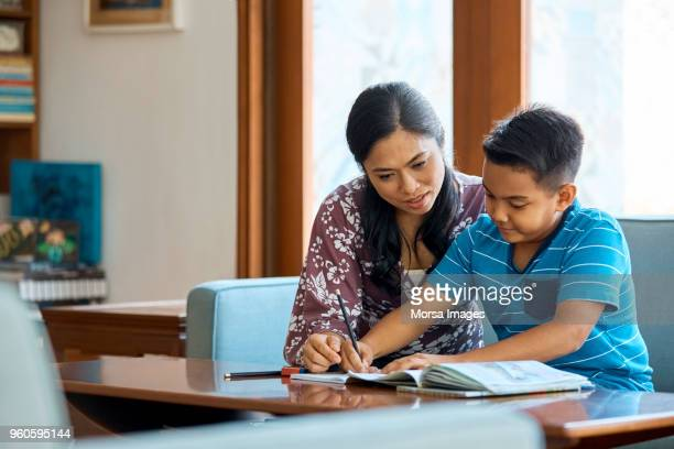 mid adult woman assisting son in studying at home - homework stock pictures, royalty-free photos & images
