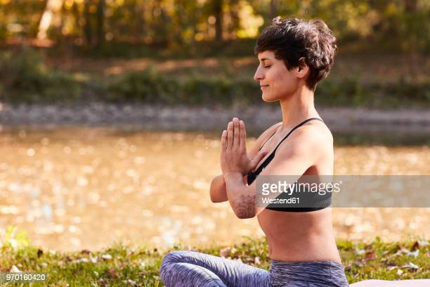 mid adult woman at riverside practicing yoga, meditation - yogi stock photos and pictures