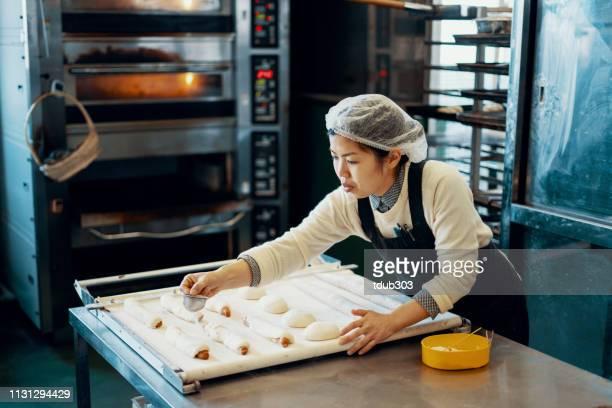 ミッドアダルト女性は、工業用キッチンでパンを焼く - パン屋 ストックフォトと画像
