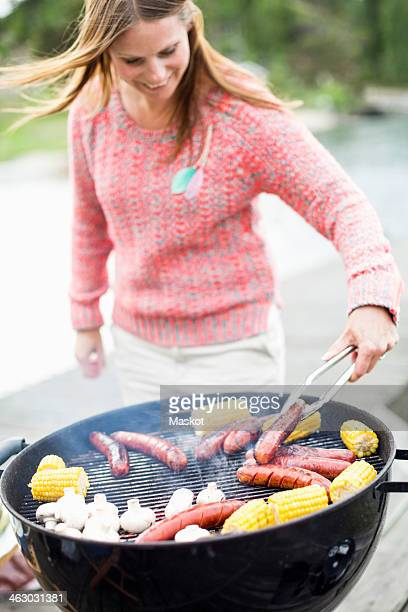 Mid adult woman barbecuing outdoors
