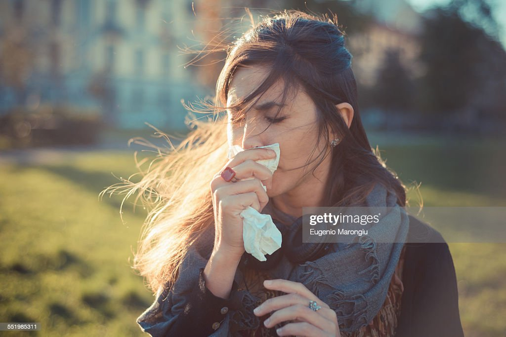 Mid adult woman blowing nose with hankerchief in park : Stock Photo