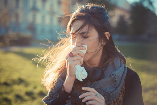 Mid adult woman blowing nose with hankerchief in park - gettyimageskorea