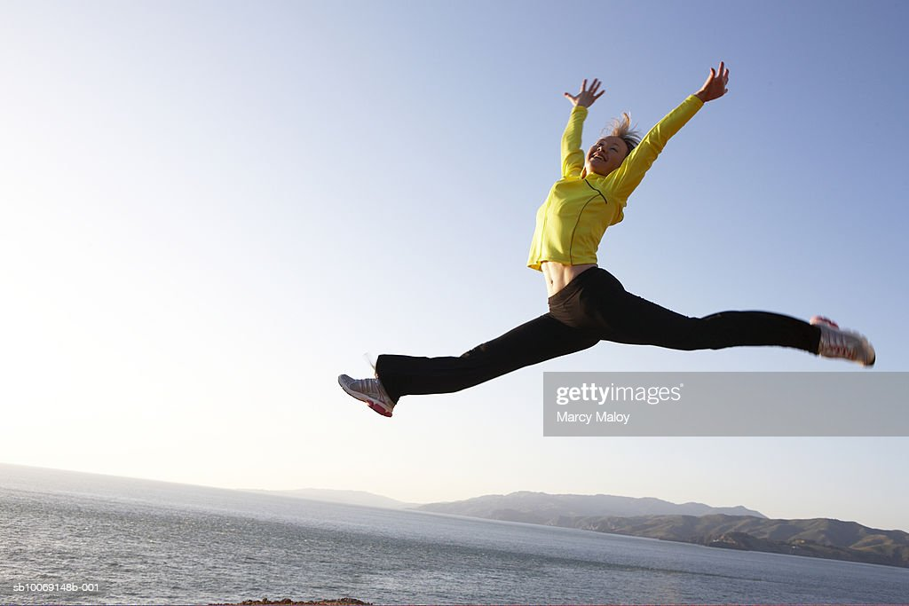 Mid adult woman by ocean, leaping into air : Stockfoto