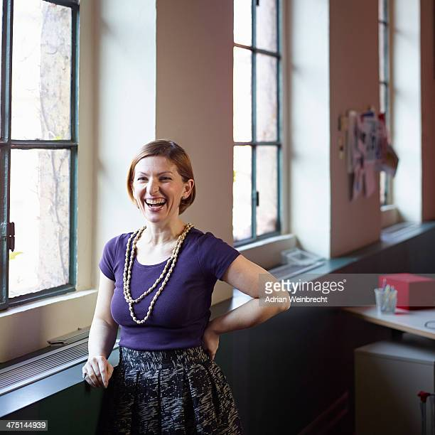mid adult woman by window, laughing - purple skirt stock pictures, royalty-free photos & images