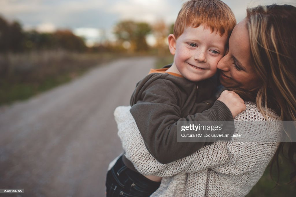Mid adult woman carrying and hugging son on rural road : Stock Photo