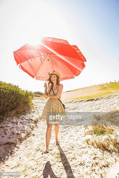 Mid adult woman carrying beach umbrella at beach, Cape Town, South Africa