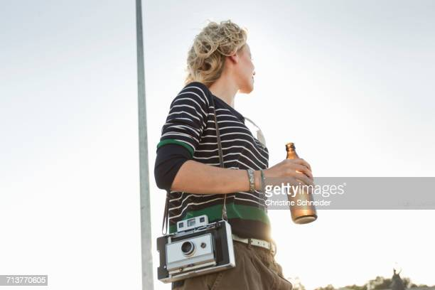 Mid adult woman carrying beer bottle and vintage camera in park