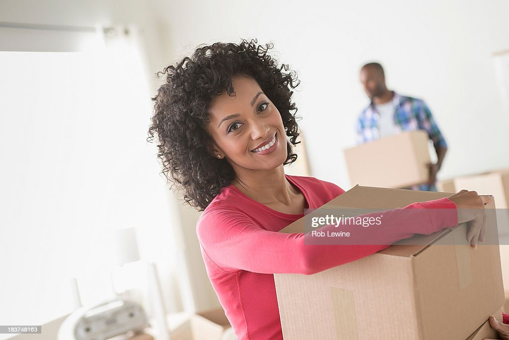 Mid adult woman carrying cardboard boxes : Stock Photo