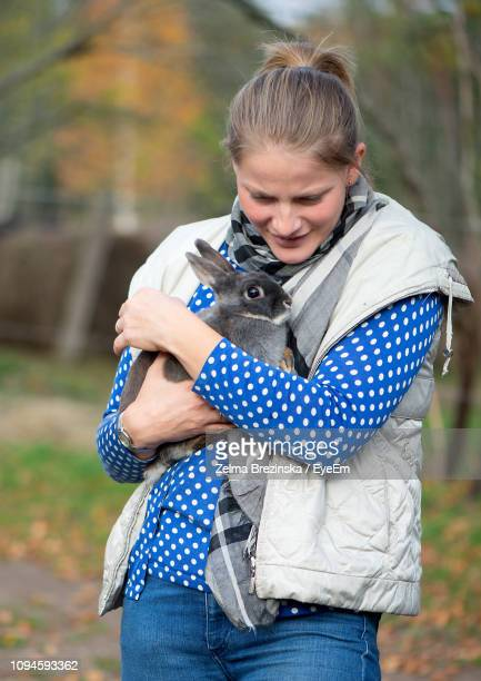 Mid Adult Woman Carrying Rabbit While Standing In Park