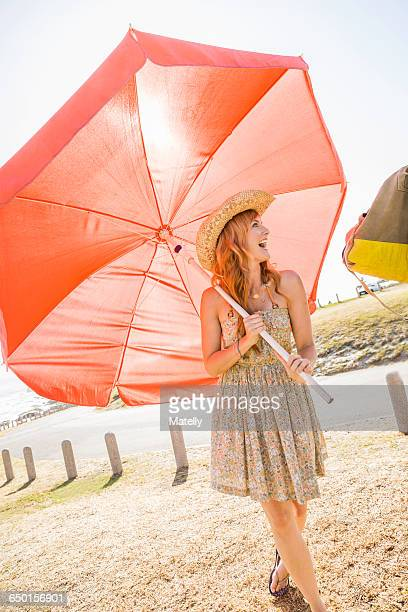 Mid adult woman carrying red beach umbrella at beach, Cape Town, South Africa