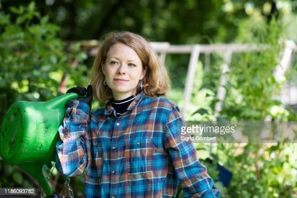 mid adult woman carrying watering can in her garden - sigrid gombert stock-fotos und bilder