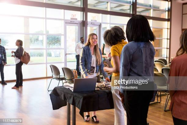mid adult woman cheerfully handles expo registration - attending stock pictures, royalty-free photos & images